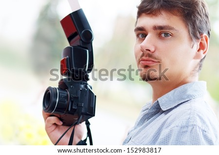 young man photographer with black professional camera and mobile flash - stock photo