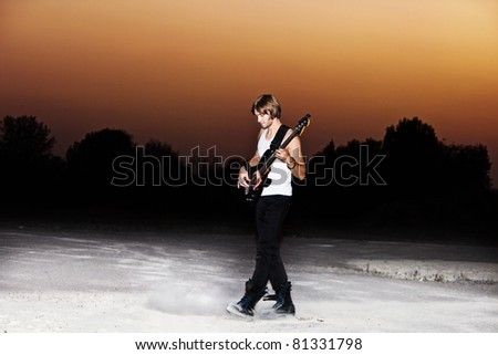 young man play electric guitar at sunset, full body shot - stock photo