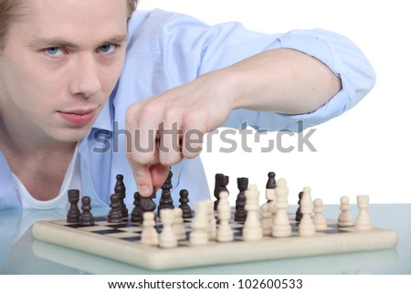 young man playing chess - stock photo