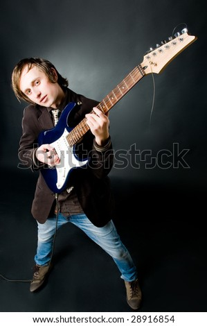 Young man playing electro guitar, high angle view - stock photo