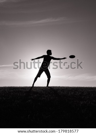 Young man playing frisbee. Young man outdoors. - stock photo