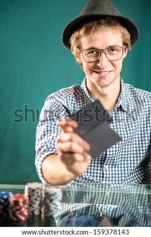 Young man playing, gambling and smiling - stock photo