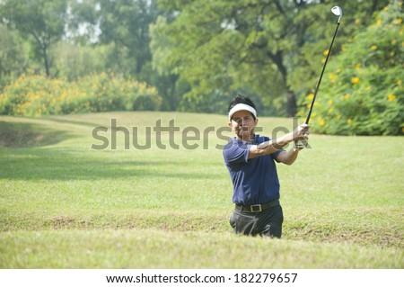 young man playing golf, golfer hitting fairway shot, swinging club  - stock photo