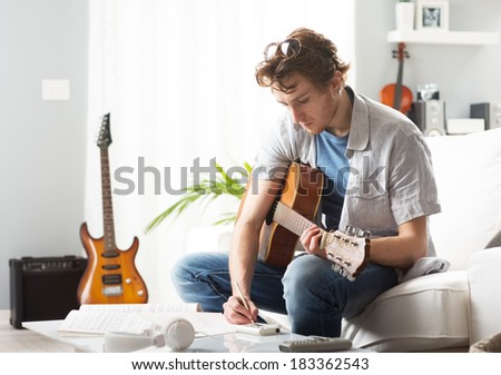 Young man playing guitar and composing a song sitting on sofa. - stock photo
