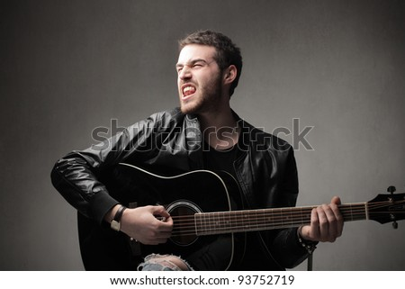 Young man playing guitar and singing - stock photo
