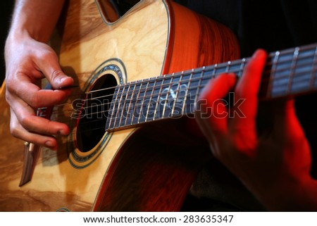 Young man playing on acoustic guitar close up - stock photo