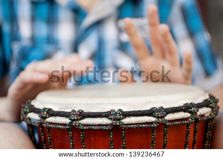 Young man playing on djembe. Shallow depth of field for emphasis on a musical instrument - stock photo
