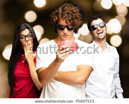 young man playing poker with friends against a abstract lights background - stock photo