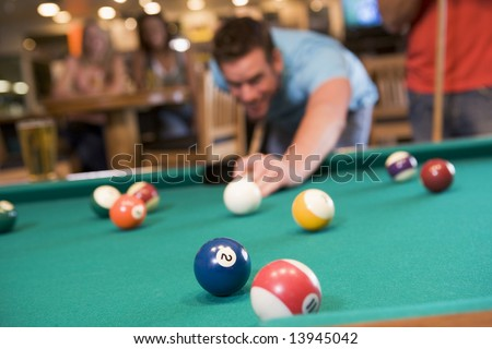 Young man playing pool in a bar (focus on pool table) - stock photo
