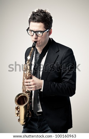 Young man playing sax on gray background - stock photo
