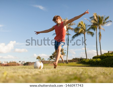 Young man playing soccer in the park - stock photo