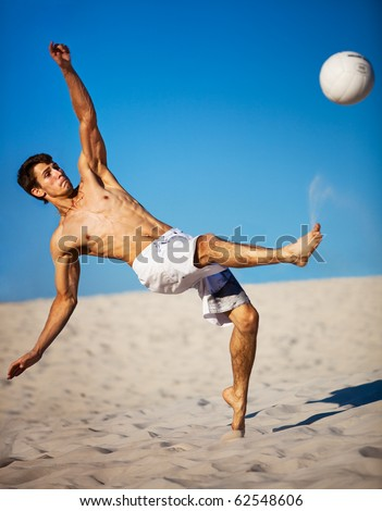 Young man playing soccer on beach. Focus on face. - stock photo