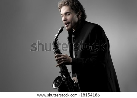young man playing the saxophone - stock photo