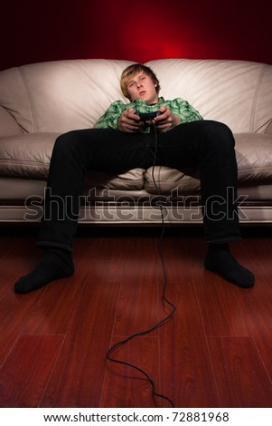 young man playing video games on red background - stock photo