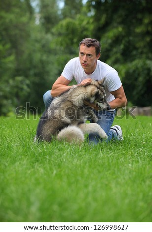 Young man playing with his Alaskan Malamute outdoors - stock photo