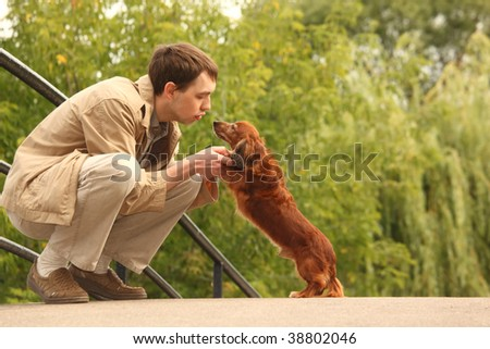Young man plays with his adorable dachshund  outdoor - stock photo