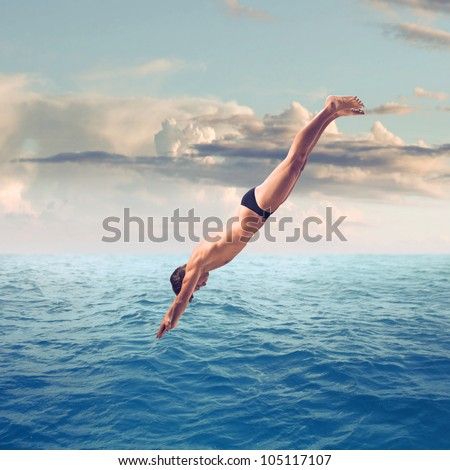 Young man plunging into the sea - stock photo
