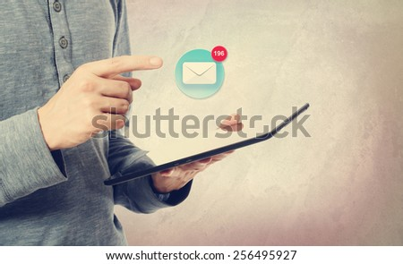 Young man pointing at an email icon over a tablet computer - stock photo