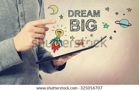 Young man pointing at Dream BIG concept over a tablet computer - stock photo