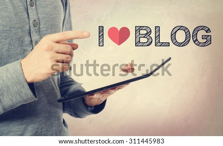 Young man pointing at I love Blog text over a tablet computer - stock photo