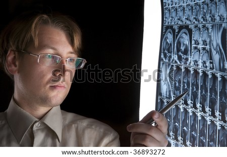Young man pointing at MRI film - stock photo