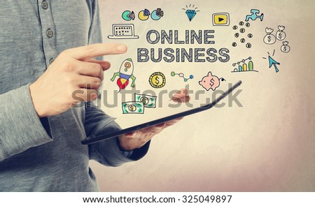 Young man pointing at  Online Business concept over a tablet computer - stock photo