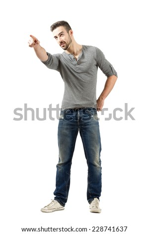 Young man pointing at something or someone in the distance.  Full body length isolated over white background. - stock photo