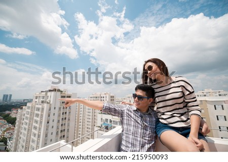 Young man pointing at something while he and his girlfriend sitting on the roof - stock photo