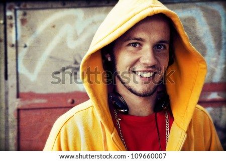 Young man portrait in hooded sweatshirt / jumper on grunge graffiti wall - stock photo