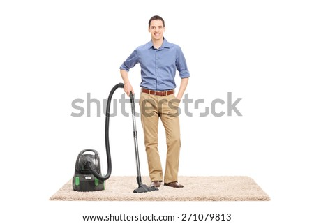 Young man posing next to a vacuum cleaner on a beige carpet isolated on white background  - stock photo