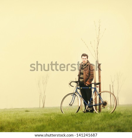 Young man posing on green meadow in the morning with vintage bike - stock photo