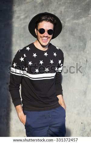 Young man posing with a trendy outfit against a urban background - stock photo