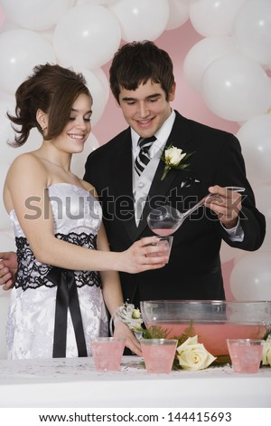 Young man pouring punch for girlfriend at prom - stock photo
