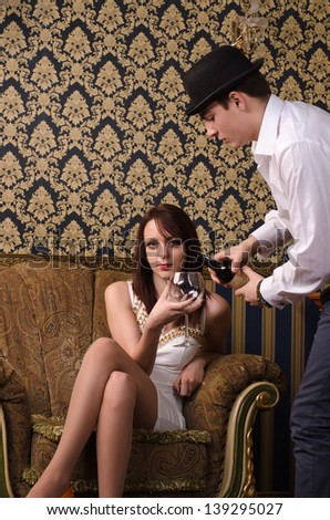 Young man pouring red wine for an elegant attractive woman in a stylish evening dress sitting in an ornately carved armchair - stock photo