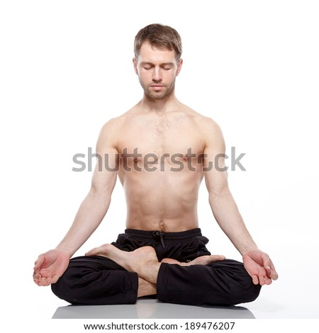 young man practicing yoga on white background, meditating in lotus position. - stock photo