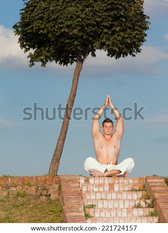 Young man practicing yoga outdoors - stock photo