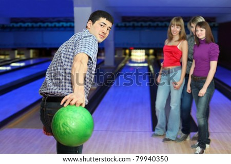 Young man prepares throw ball on path for bowling and three girls look on him, focus on man - stock photo