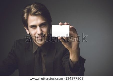 Young man presenting a business card - stock photo