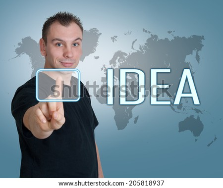 Young man press digital Idea button on interface in front of him - stock photo