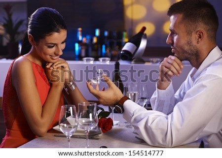 Young man proposing to beautiful woman, holding engagement ring, waiting for answer. - stock photo