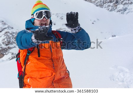 Young man protecting face from snowballs in winter mountains - stock photo