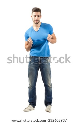 Young man pulling or tearing t-shirt.  Full body length isolated over white background. - stock photo