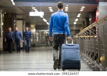 Young man pulling suitcase in modern airport terminal. Travelling guy wearing smart casual style clothes walking away with his luggage while waiting for transport. Rear view. Copy space - stock photo
