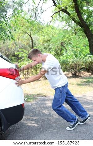 Young man pushing broken down car - stock photo