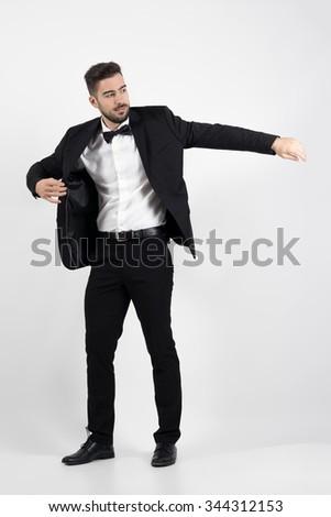 Young man putting on black suit tuxedo coat.  Full body length portrait over gray studio background. - stock photo