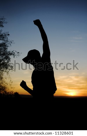 Young man raising his fist in the air for joy. - stock photo