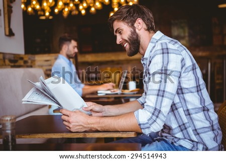 Young man reading a newspaper in a coffee shop - stock photo