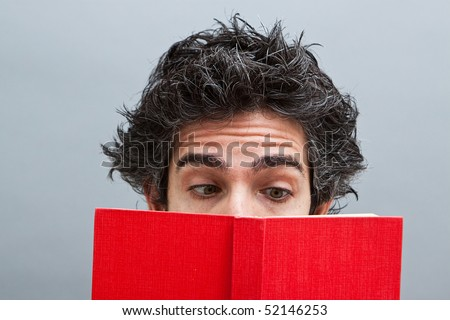 Young man reading a red book - stock photo