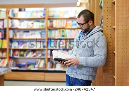 Young man reading book in the library - stock photo