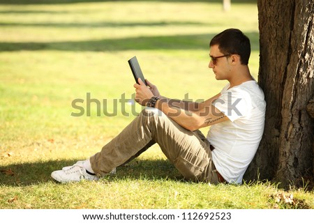 young man reading news on tablet - stock photo